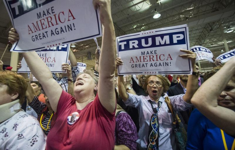 Supporters Kathleen Hastings, left, and Elizabeth Musngi, right, cheers Republican presidential candidate Donald Trump as he speaks during a campaign rally held at the North Atlanta Trade Center, Saturday, Oct., 10, 2015, in Norcross, Ga.