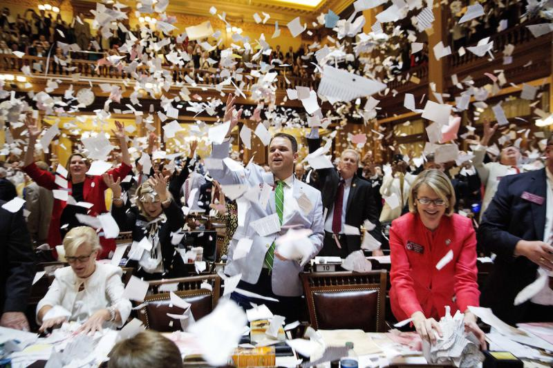 State Rep. Christian Coomer, R-Cartersville, center, and fellow lawmakers throw up paper from their desks at the conclusion of the legislative session in the House chamber, in Atlanta, Friday, March 31, 2017.