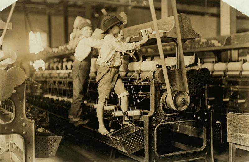 Some boys, like these two in Macon, Georgia, were so small they had to climb up on the spinning frame to mend the broken threads and put back the empty bobbins. This photo was taken in 1909.