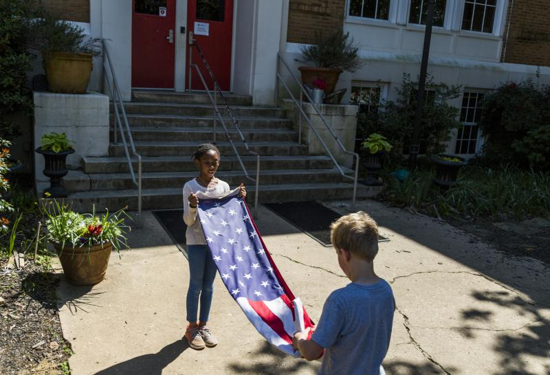 Summer Hardeman, left, and Xander Zimmerman fold the flag near the end of the school day at Atlanta Neighborhood Charter School.
