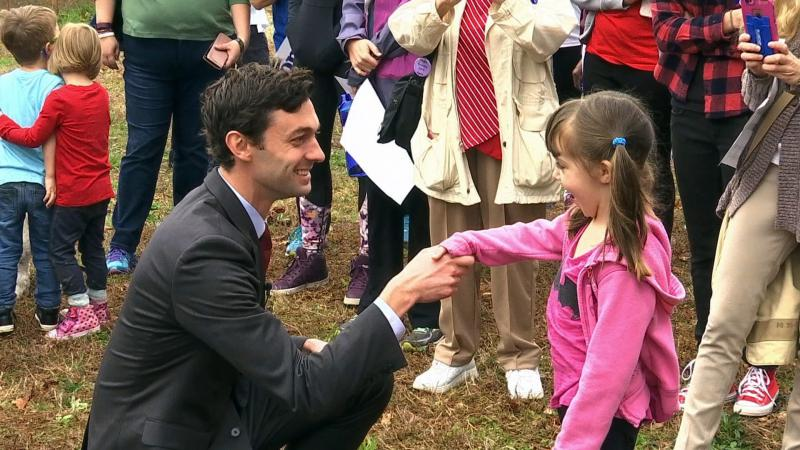 In a Monday, March 27, 2017 photo, Democratic congressional candidate Jon Ossoff is seen with supporters outside of the East Roswell Branch Library in Roswell, Ga., on the first day of early voting.