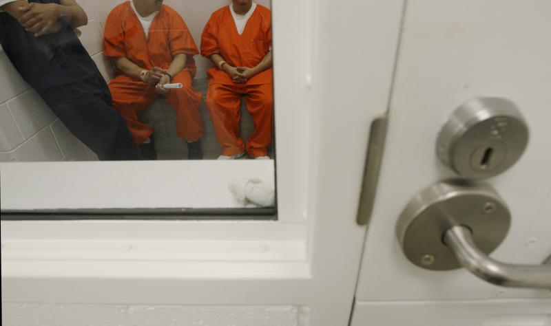 In this photo taken on Friday, Oct. 17, 2008, detainees are shown inside a holding cell at the Northwest Detention Center in Tacoma, Wash. The facility is operated by The GEO Group Inc. under contract from U.S. Immigrations and Customs Enforcement.