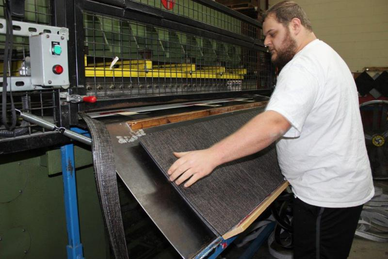 A worker guides the creation of high-end vinyl placemats, table, floor and wall coverings at the Chilewich textile factory in Murray County, Georgia.