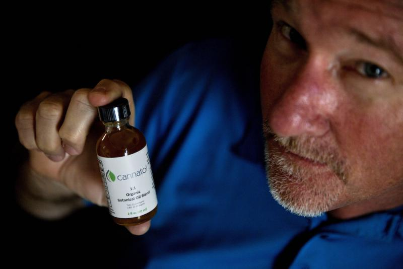 In this Monday, April 17, 2017 photo, Georgia State Rep. Allen Peake, R - Macon, displays a bottle of cannabis oil in his office in Macon, Ga. Peake is at the center of a semi-legal statewide medical cannabis distribution network.