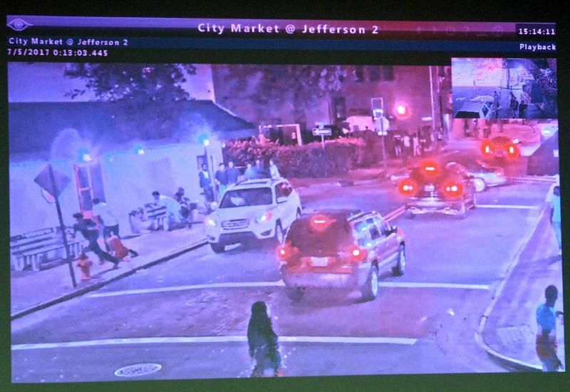Surveillance video footage shows a white SUV, left, drive slowly past a sidewalk bench where several people in Savannah were gathered before they started running as gunshots were fired.