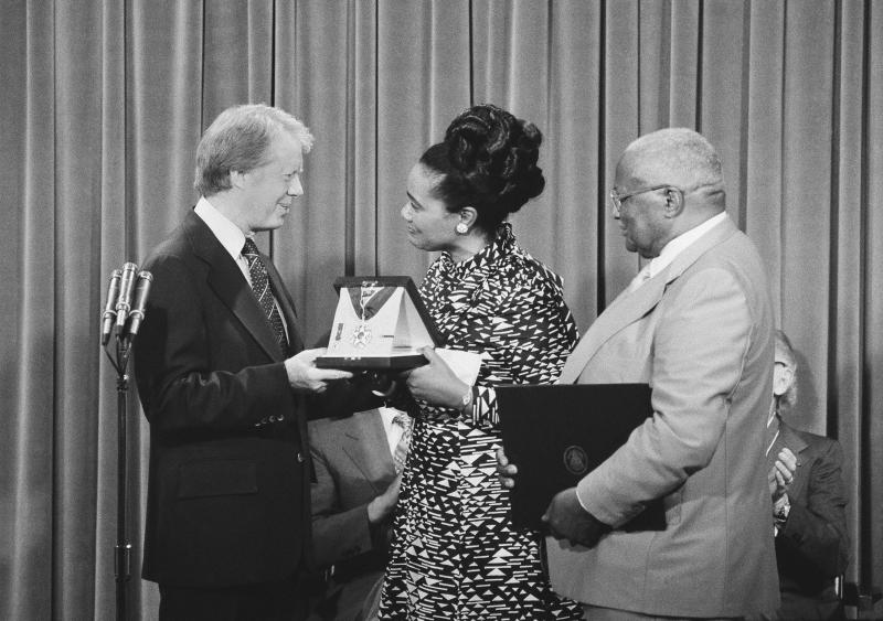 President Jimmy Carter presents the Medal of Freedom Award to Coretta King, wife of the late Dr. Martin Luther King, during a ceremony at the White House in 1977. At right is Martin Luther King, Sr., father of the slain civil rights leader.