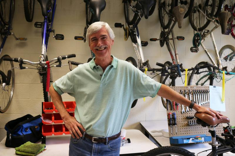 Nathan Watson poses in front of a wall of bikes at the Learn and Earn Bike Shop in Macon.
