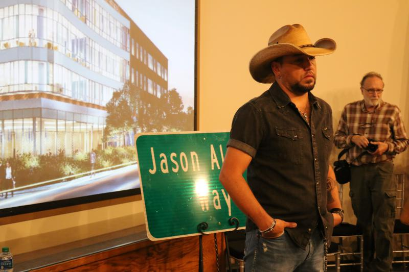 "Jason Aldean, The Academy of Country Music's reigning ""Entertainer of the Year,"" poses in front of the newly unveiled street sign named in his honor."