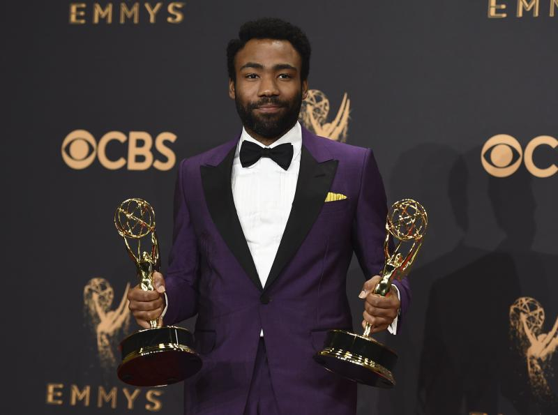 "Donald Glover poses in the press room with his awards for outstanding lead actor in a comedy series and for outstanding directing for a comedy series for ""Atlanta"" at the 69th Primetime Emmy Awards on Sunday, Sept. 17, 2017."