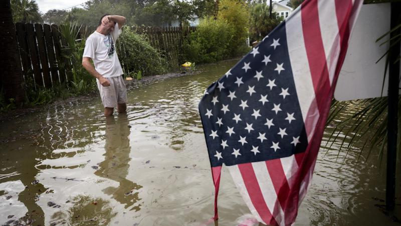 Tybee Island resident Joe Murphy wipes the sweat off his face while standing in knee deep water from Tropical Storm Irma outside his house, Monday, Sept., 11, 2017, on Tybee Island, Ga.