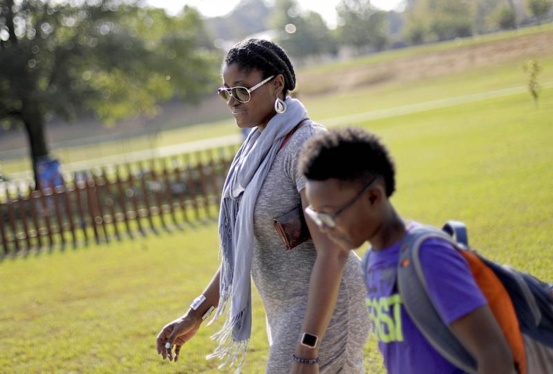 Corrie Davis, left, picks up her son Turner from Big Shanty Elementary School in Kennesaw, Ga., Wednesday, Oct. 11, 2017.