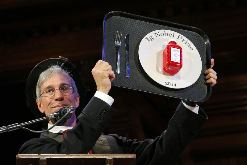 Ig Nobel Founder Marc Abrahams holds up an Ig Nobel Prize trophy.