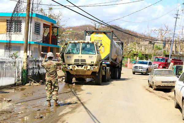 A Puerto Rico Army National Guardsman guides a truck transporting water.