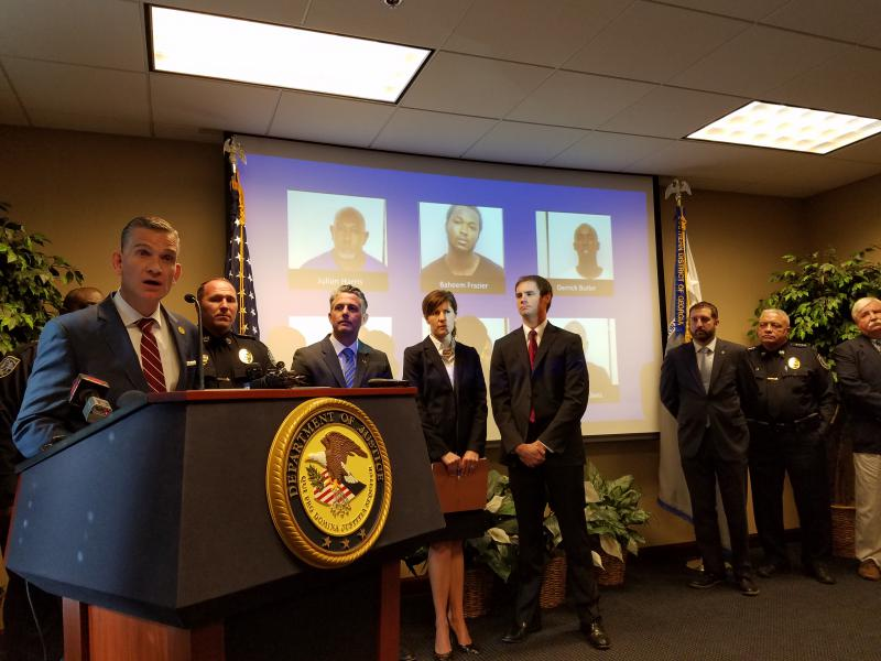 U.S. Attorney Bobby Christine announces charges against 30 Savannah residents following an investigation of two rival gangs. Behind him are photos of the six suspects still at large.
