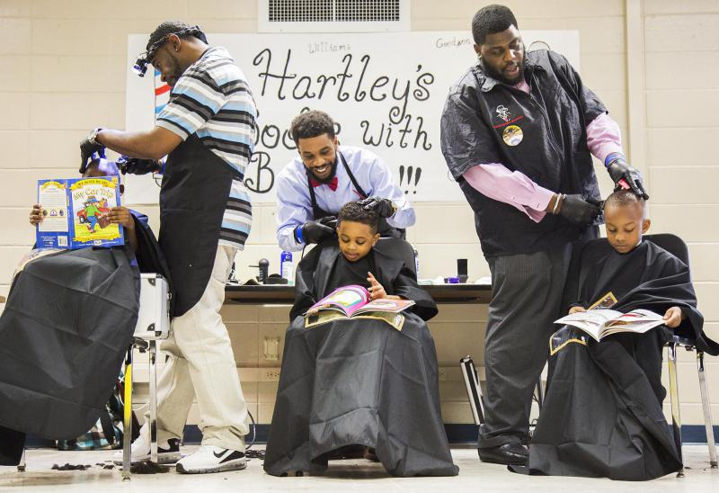 Barbers, from right, Lewis Foster III, Wade White and Derrick Brown, cutting hair and reading books  at Hartley Elementary School in Macon.