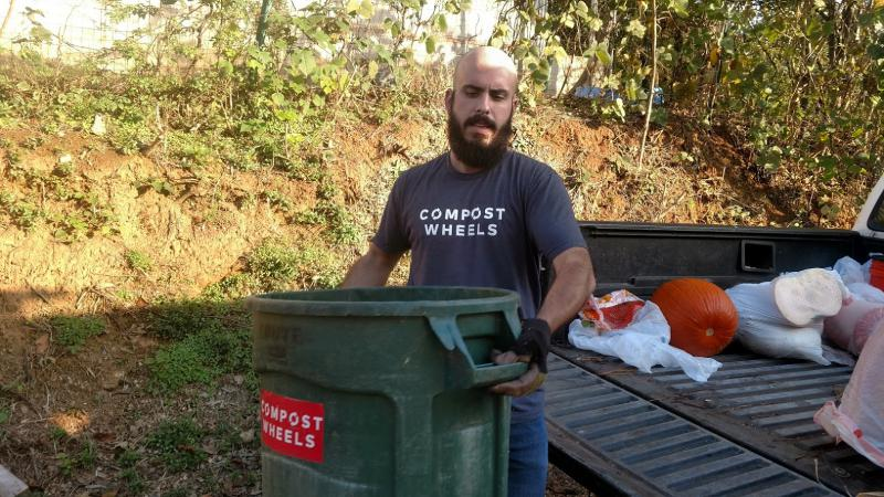 Whit Whitmire of Compostwheels carries a bucket full of food waste that he's collected during the day. He'll put this in a compost pile at Freewheel Farm in Atlanta.