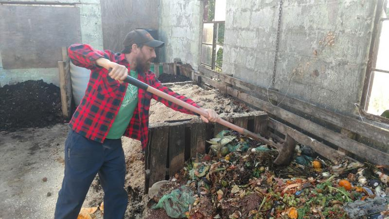 Brent Hall of Freewheel Farm mixes up a compost pile at his farm.
