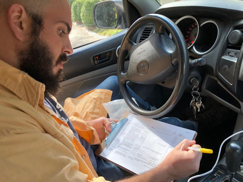 Whit Whitmire of Compostwheels checks a list of homes he has to visit to pick up food waste that will eventually be turned into compost.