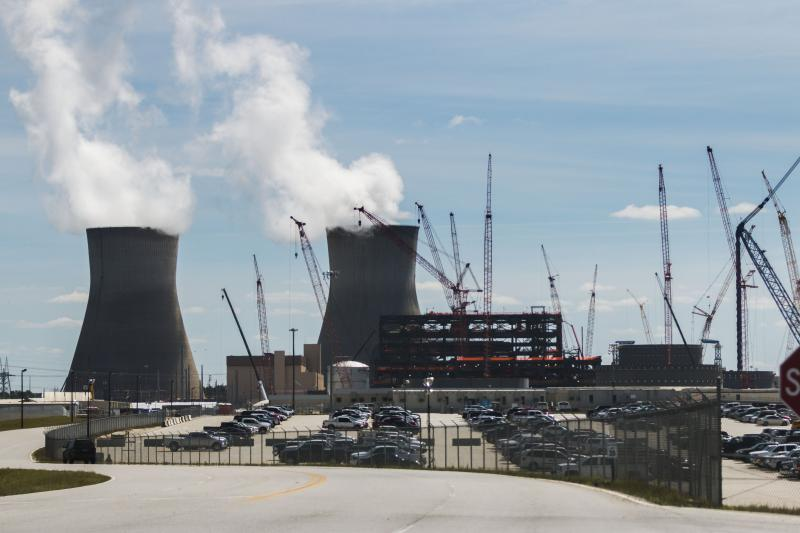 The cooling towers of the up and running #1 and #2 reactors at Plant Vogtle next to the construction cranes erecting reactors #3 and #4 in April, 2017.