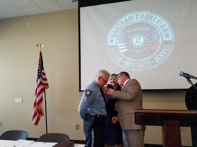 Chatham County Police Chief Jeff Hadley gets his new badge from County Manager Lee Smith.