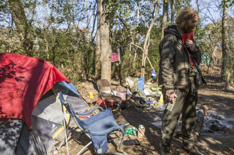 "Billy Mitchell holds a New Testament he pulled from a pocket in his coat at his campsite by the Ocmulgee River in Macon. Mitchell and others camping there are being evicted. ""Two hots and a cots.  We're all going to end up in jail,"" he said."