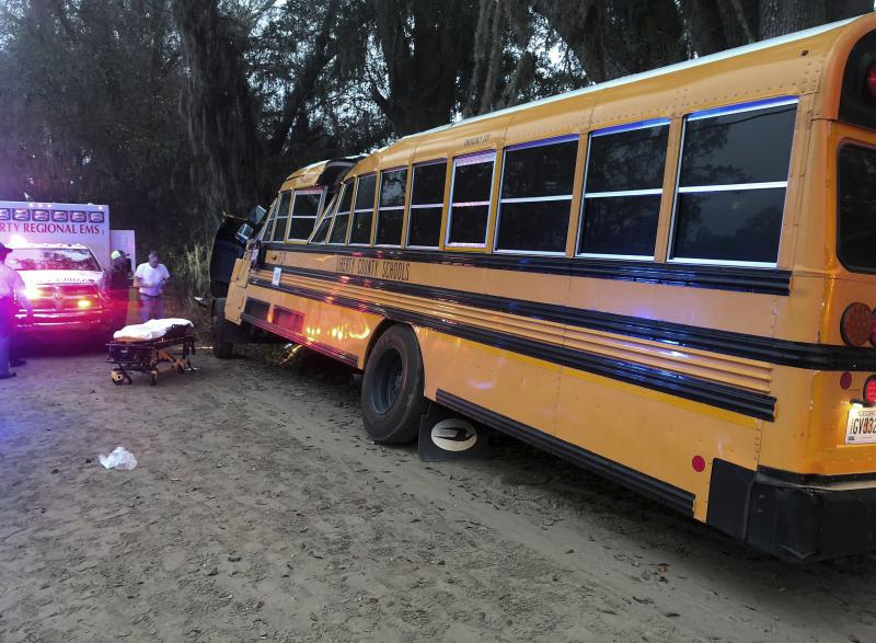 Authorities investigate the scene where a school bus crashed, Tuesday, Dec. 5, 2017, in Gum Branch, Ga. Liberty County Public Safety Director Mike Hodges said more than 20 children were riding the bus when it crashed into a tree during its morning route.