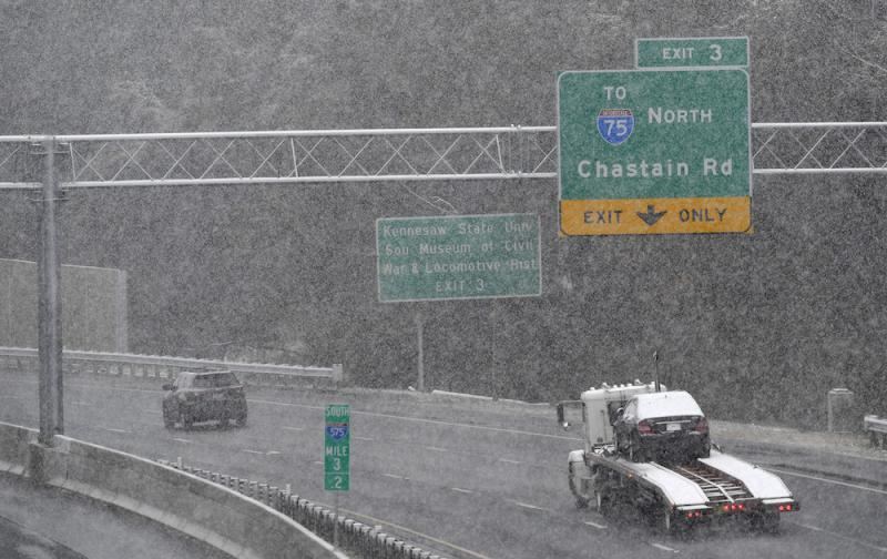 Traffic moves south in a moderate snow, Friday, Dec. 8, 2017, in Kennesaw, Ga. The forecast called for a wintry mix of precipitation across several Deep South states.