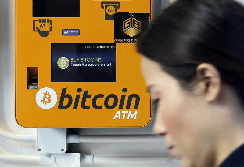 In this Dec. 21, 2017 file photo, a woman walks past the Bitcoin ATM in Hong Kong.
