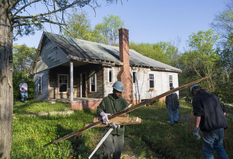 "A crew works to demolish a home in Macon's Linwood Estates neighborhood in 2015. The original, Federal redlining maps from the 1930s said of Linwood ""subdivision failed before depression began."""