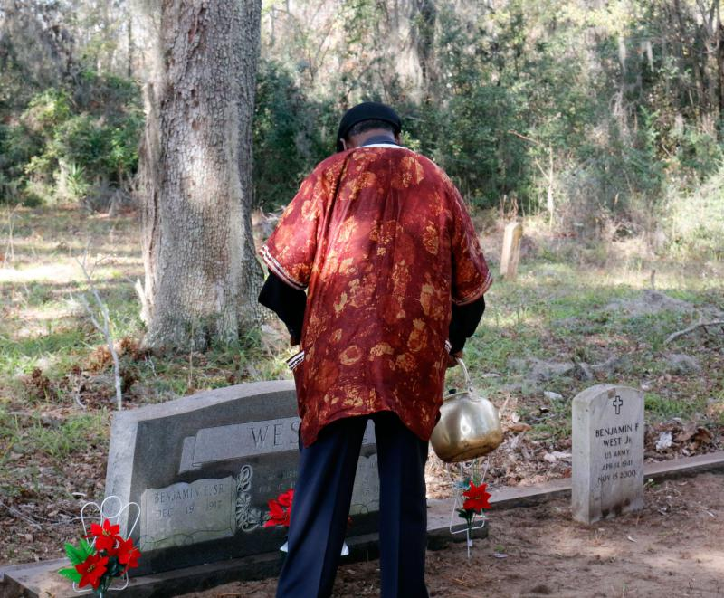 Freddie uses a ceremonial tea kettle to annoint the gravesite.