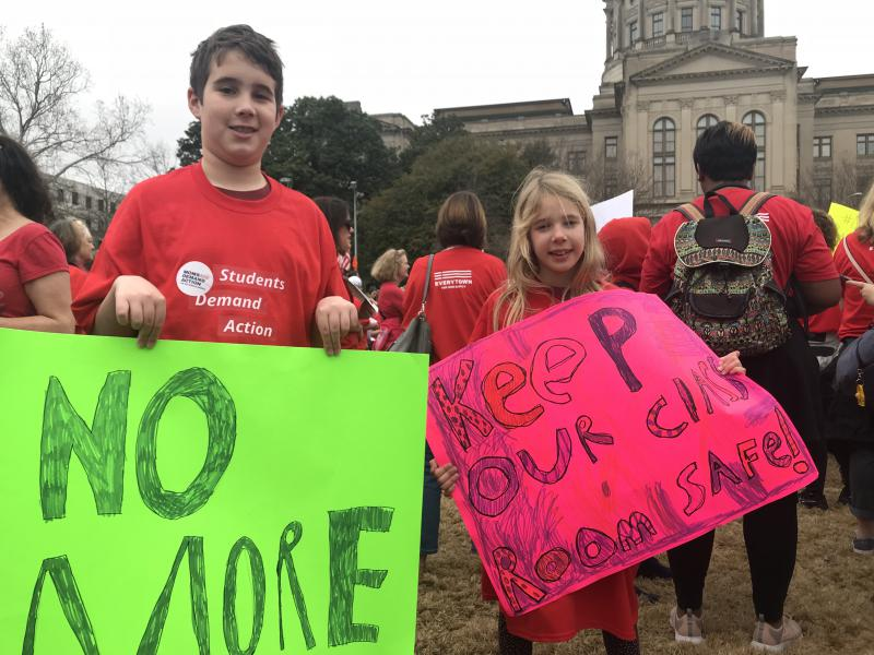 Ben Trussell, 10, and Chloe Trussell, 7, both of Kennesaw, Georgia, hold signs at the Moms Demand Action for Gun Sense rally.