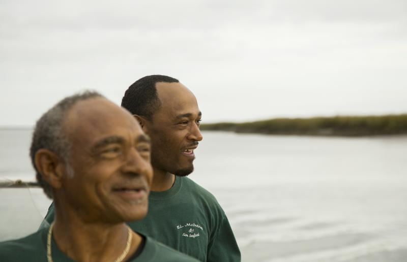 Earnest McIntosh, Jr., right, grew up watching his father, Earnest Sr., left, at work on a crab boat on the waters near their home in McIntosh County. Today they are trying to make a go of farming oysters together.
