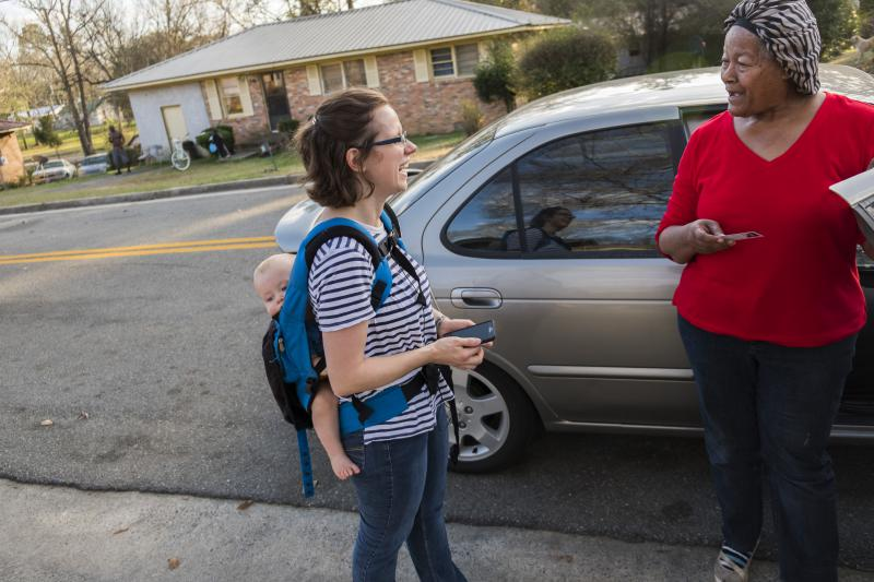 Cheyenne Warnock, left, carrying one of her four children, talks with Shirley Home during Warnock's first day of door to door canvassing in Cochran in her run for a Georgia legislative seat.