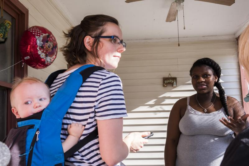 Cheyenne Warnock, left, candidate for a Georgia House of Representatives seat talks with Deandrea Baker on the porch of her Cochran home during Warnock's first day of door to door canvassing.