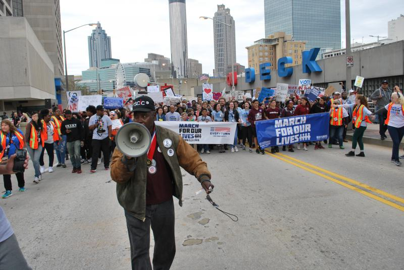 """General"" Larry Platt leads the way for student marchers. Platt earned his nickname during the Civil Rights Movement."