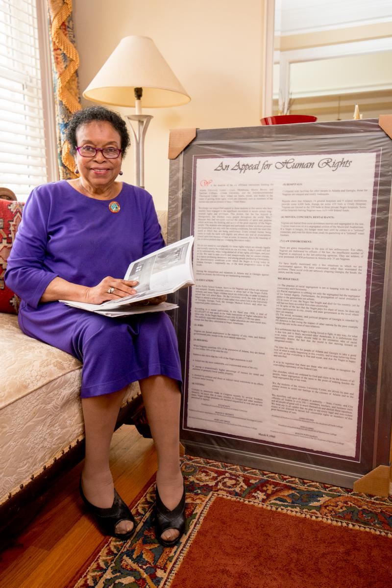 "Dr. Roslyn Pope in her home next to her framed ""Appeal for Human Rights"" document."