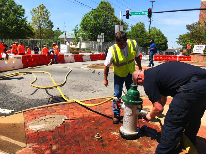 Public safety workers use a fire hydrant to fill up water barricades the City of Newnan rented for the weekend.