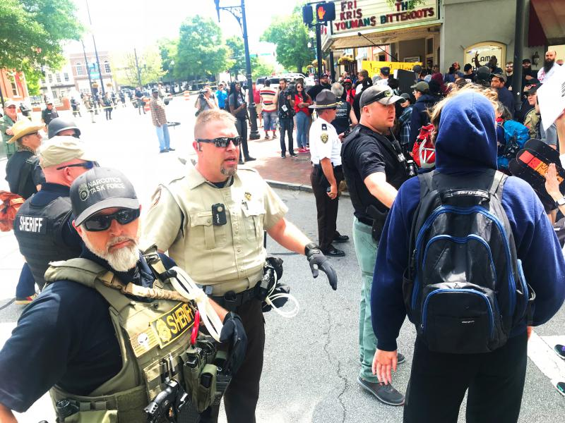 Law enforcement demanded that this marcher in a blue hoodie remove his mask.