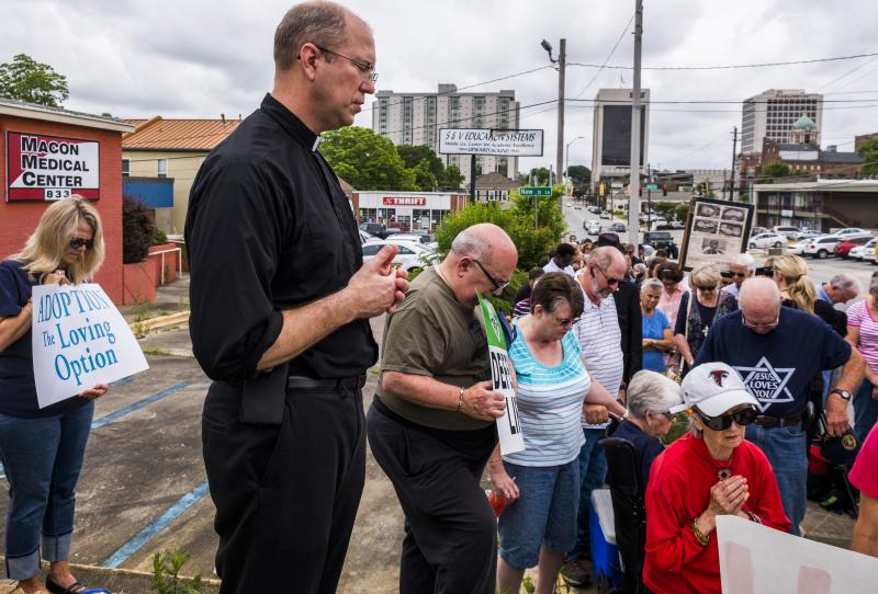 Father Scott Winchel of Macon's St. Joseph's Catholic Church leads protesters in prayer outside the proposed location of the Summit Medical Center in Macon. The clinic would be the first abortion provider in Macon in decades.
