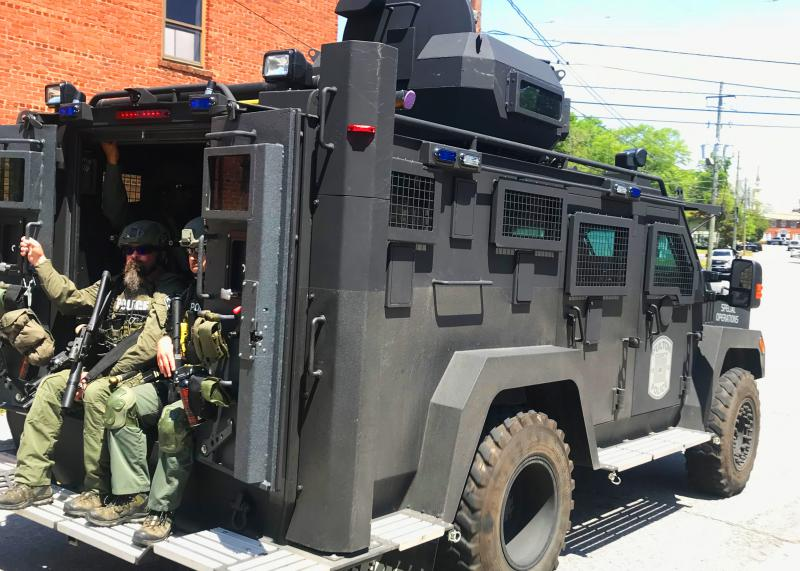 An armored convoy rolls down one of Newnan's closed streets on April 21, 2018.