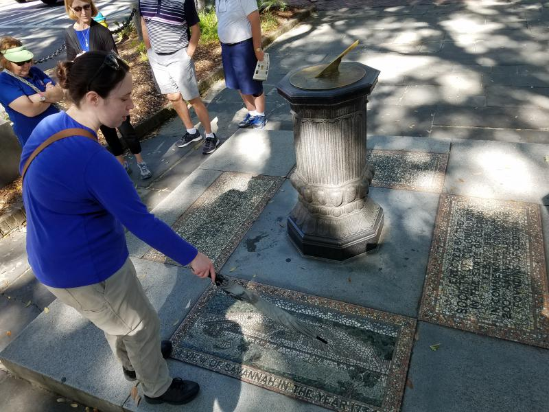 "Tour guide Bonnie Terrell explains Savannah's historic street plan  a grid broken up by parks called ""squares"" — with the help of a mosaic in Johnson Square."