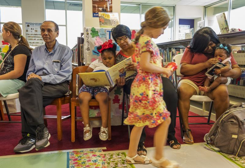 Johnnie Prater, center, reads to her granddaughter at the Riverside Library in Macon Friday.