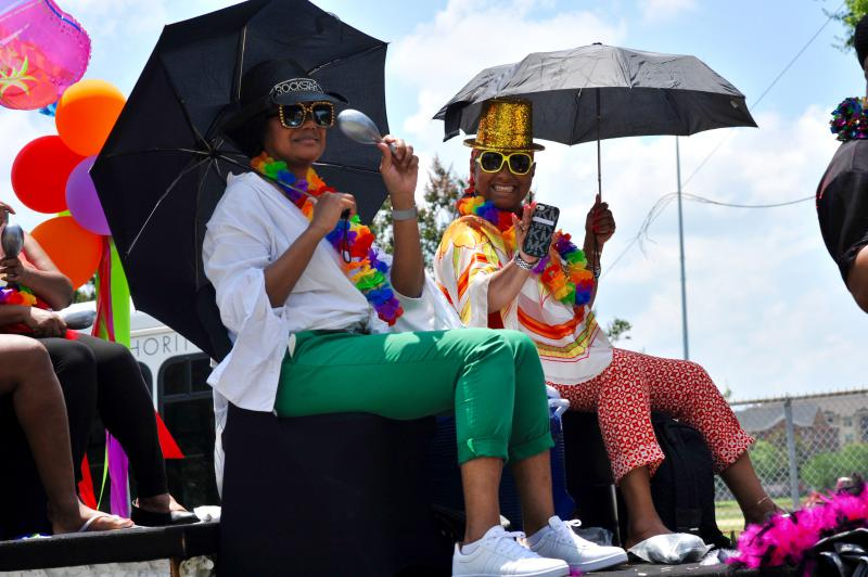 Two women celebrating the Juneteenth festival on one of the colorful floats in the parade.