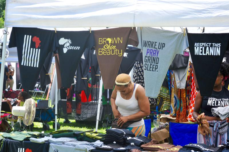 """""""Black excellence"""" and """"melanin magic shirts"""" hang at a vendor's tent at the Juneteenth Festival."""