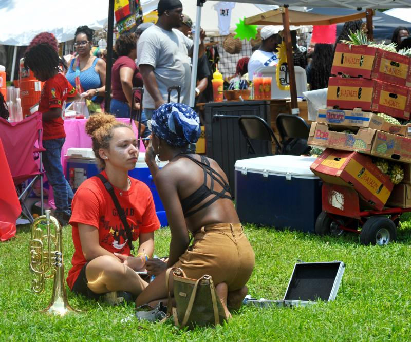 A vendor paints traditional tribal face paint on a girl from a high school band who was in the festival's parade.