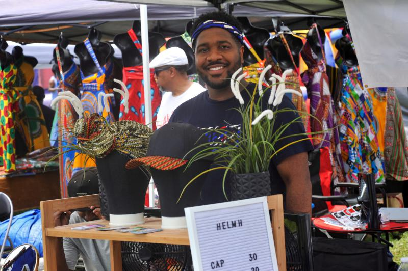 Harlam Duru is a vendor at the fesitval. His company's name is Healm, they do headwraps and create festive hats.