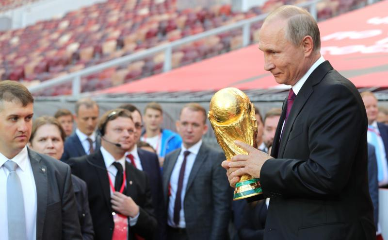 Russian president Vladimir Putin holding the FIFA World Cup Trophy at a pre-tournament ceremony in Moscow, September 2017
