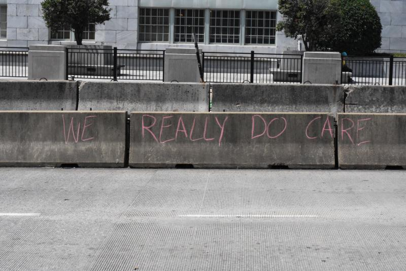 Protesters write in chalk during Atlanta Families Belong Together march June 30