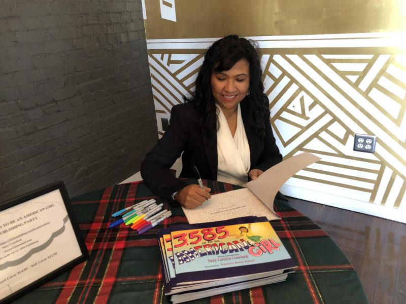 "Author of ""3,585 Miles to be an American girl"", Nury Castillo-Crawford signs a page of her book at a book release."