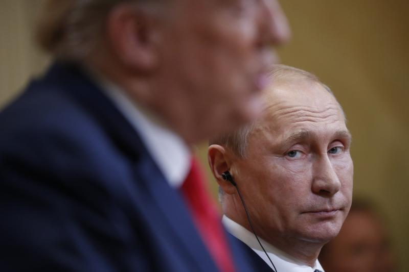 Russian President Vladimir Putin looks over towards U.S. President Donald Trump as Trump speaks during their joint news conference at the Presidential Palace in Helsinki, Finland.